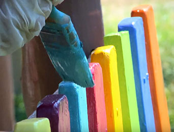 Painting a fence bright colors.